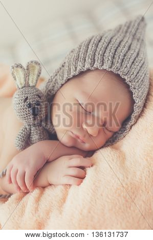 Cute girl in a gray knitted cap,put the handle under his head and hugging toy gray Bunny with big ears, sleeping on a pink blanket on a gray background