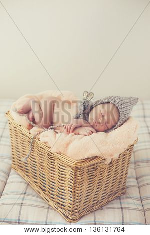 Adorable little guy with little fluffy hairs,in a gray knitted cap,tucked under his legs and put the handle under his head,sound asleep on the soft beige blanket in a large wicker basket high,sweet sleeping newborn baby