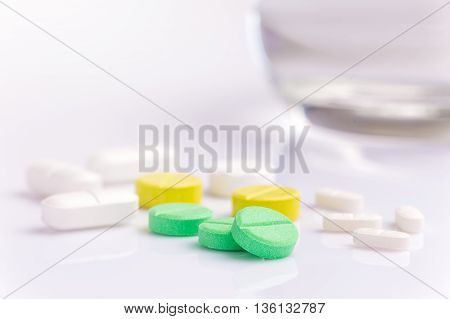 Medicine pills in various shapes colors and sizes on white background with selective focus on the front green pill with blur glass of water in the background room for copyspace on the top