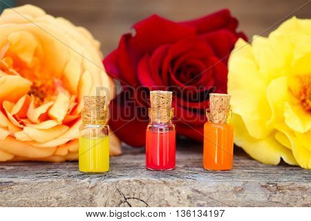 Bottles of essential oil and roses on old wooden background.