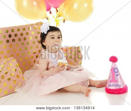 An adorable baby girl happily sitting with her mouth covered in white cupcake frosting.  She's surrounded by wrapped gifts, balloons and a first birthday party hat.  On a white background.