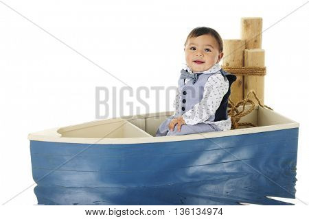 An adorable baby boy happily sitting in a small row boat next to mooring posts.  On a white background.