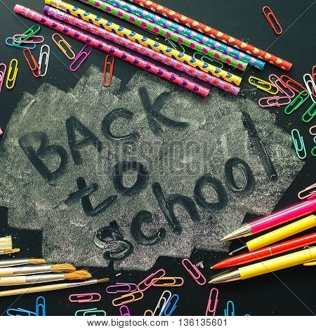 Back to school concept. School supplies on blackboard background. Back to school concept with stationery. Schoolchild and student studies accessories. Top view. Square.