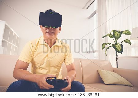 Portrait of adult man in VR glasses using controller when playing game