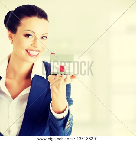 Female businesswoman holding and protecting house.