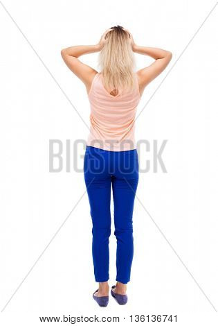 Back view of shocked woman. upset young girl. Rear view people collection.  backside view of person.  Isolated over white background. Blonde in blue pants is holding his head in horror.