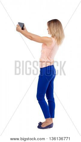 back view of standing young beautiful  girl with tablet computer in the hands of. girl  watching. Rear view people collection.  Blonde girl in blue trousers does photographed on a tablet computer.