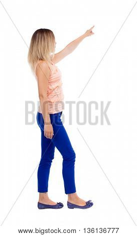 back view pointing walking woman. going girl pointing. backside view person.  Rear view people collection. Isolated over white background. Girl in blue trousers leaves left looking at something in sky