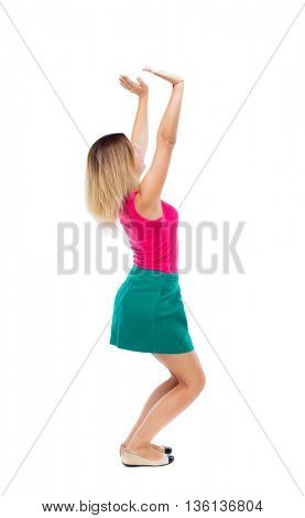 back view of woman pushes wall. Isolated over white background. backside view of person. blonde in a green skirt and pink blouse sitting down holding something heavy over his head