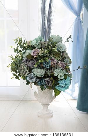a bouquet of artificial flowers in the vase on the table
