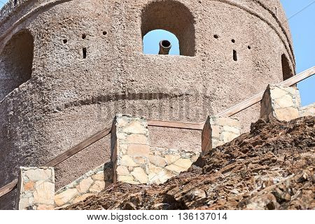 Watch tower of a fort with a cannon in the ramparts against a blue sky
