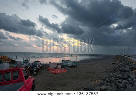 Fishing boats and a pickup on a beach at sunrise against a cloudy sky breaking into golden hues as the sun rises