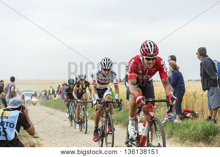 Quievy, France - July 07 2015: Group of four cyclists riding on a cobblestone road during the stage 4 of Le Tour de France 2015 in Quievy France on 07 July2015.