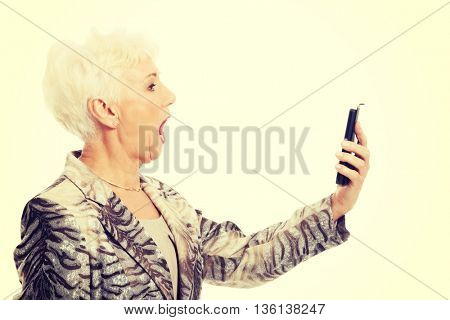 An old elegant lady using mobile phone.