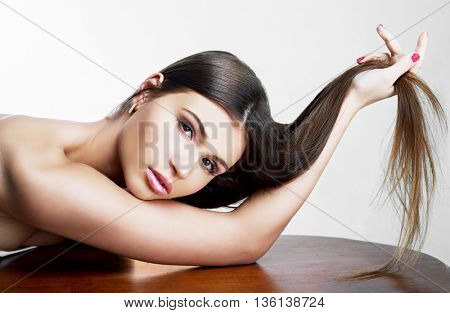 beautiful slim model with long hair,  against light background