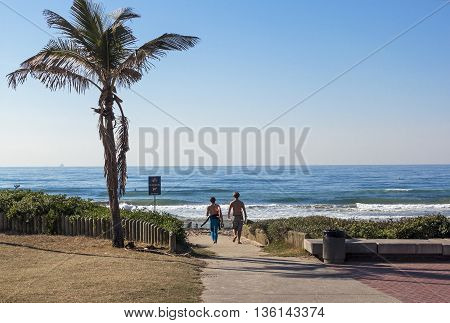 Young Boys Walking Onto Beach Past Palm Tree