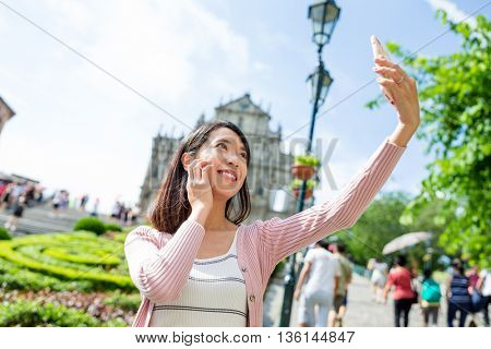 Woman taking selfie with Saint Paul's Cathedral in Macau