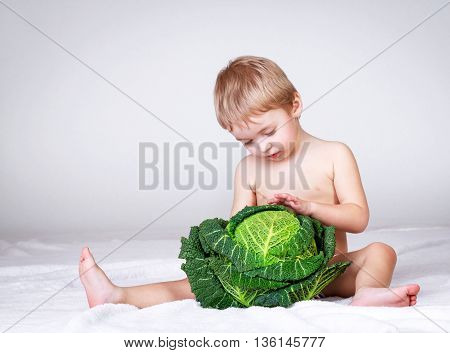 Boy with cabbage studio shot gray background