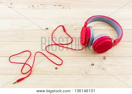 Red Headphones on the wood desk Background.