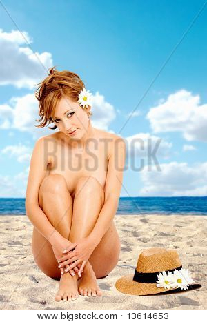 beautiful nude girl at the beach smiling and sitting on the floor isolated over a white background