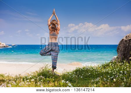 Lady stretching on the sandy beach standing on one leg