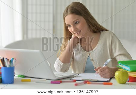 Portrait of a cute teenager girl using computer
