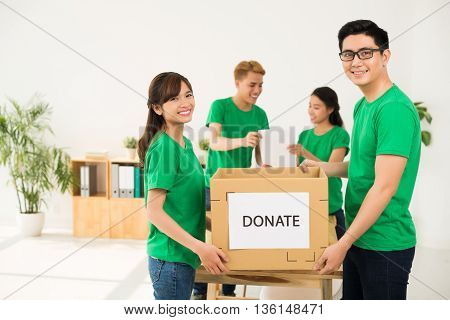 Young Asian volunteers holding cardboard box with donate inscription