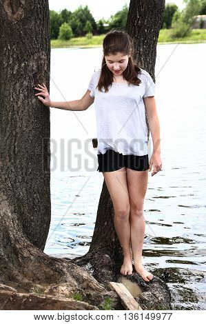 teenager girl try water in the lake with her foot
