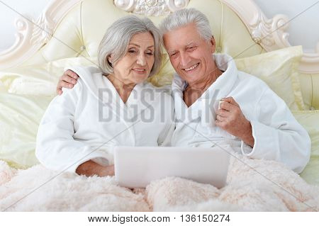 happy Senior couple  in bed with laptop