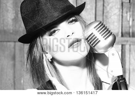 young pretty woman with sexy lips singing into silver studio microphone in retro hat and braces on shirt with bow closeup black and white