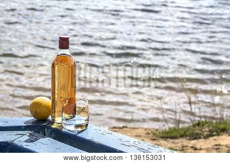 Bottle of whiskey and tumbler with lemon on the shore of lake