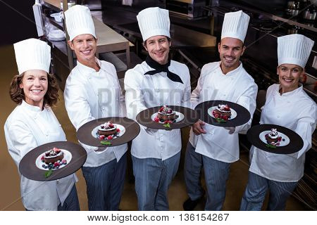 Happy chefs presenting their dessert plates in commercial kitchen