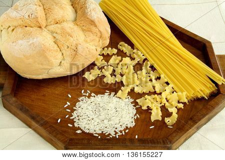 Carbohydrates: pasta, rice, bread on a wooden tray.