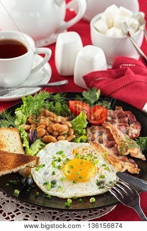 Traditional English breakfast with bacon, fried egg, beans with tomato sauce, lettuce, cherry tomatoes and toasted bread