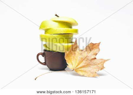 Fresh green cut apple lying in pyramid on brown coffee cup near autumn maple leaf isolated on white background