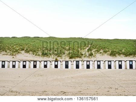 Beach huts or houses and blue sky. Beach bathing huts with white sand and clear blue sky. Beach scene with copy space. Front view.