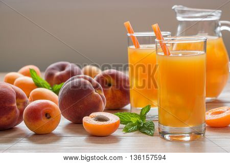 Apricot and peach juice in glasses with ice near the jar of juice and scattered apricots and peaches mint on a light wooden background. Apricot and peach juice with ice. Horizontal. Daylight. Close.