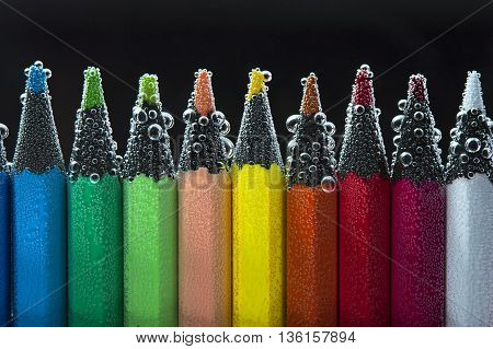 Colorful pencils in sparkling water. Back to school concept.