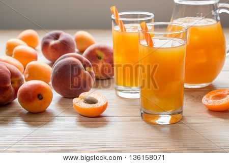 Apricot and peach juice in glasses with ice near the jar of juice and scattered apricots and peaches on a light wooden background. Apricot and peach juice with ice. Horizontal. Daylight. Close.