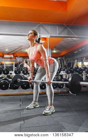 Female athlete intensive training with barbell. Professional female sportsman doing strenth exersices at gym with barbell. Squatting with barbell girl