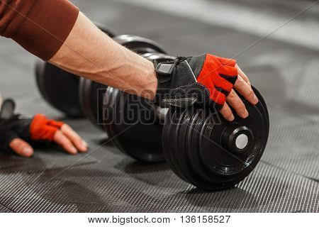 Male hand touching dumbbell on gym floor closeup. Unrecognizable athlete and two dumbbells. Beginning of powerful workout with weights in gym