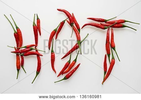A shot of red chillies arranged to spell hot on a white background.