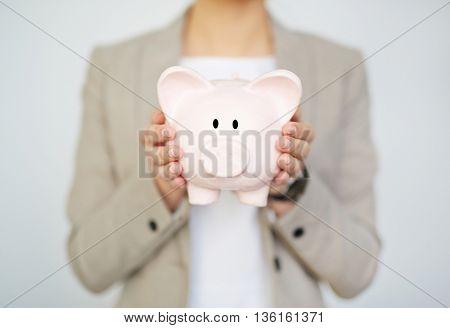 Unrecognizable businesswoman holding piggy bank