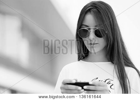 Black And White Portrait Of Beautiful Young Stylish Woman Uses Smartphone
