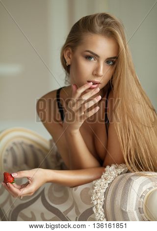 Beautiful and sexy young blonde woman lying on bed eating strawberries