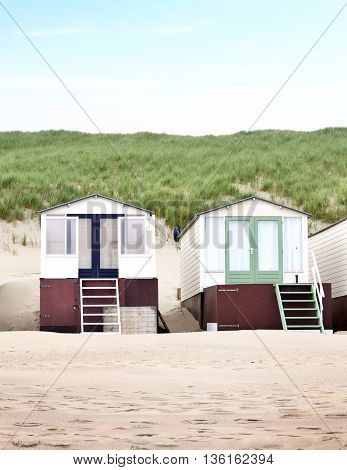 Beach huts or houses and blue sky. Multicolored beach bathing huts with white sand and clear blue sky. Beach scene with copy space. Frontal view.