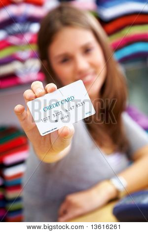 woman holding a credit card in a shop - please note the creditcard numbers are made up