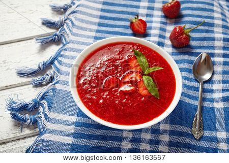 Natural organic fresh strawberry cream soup vegetarian cold sweet berry smoothie summer food on white wooden background table