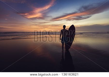 Surfer on the ocean beach at sunset on Bali island, Indonesia