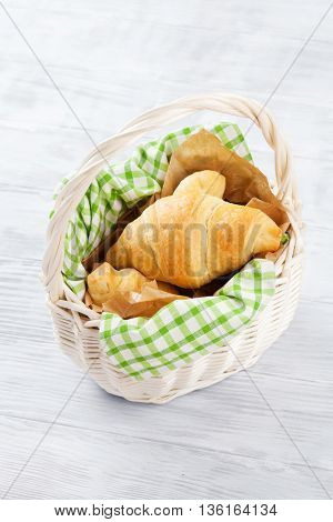 Fresh croissants basket on wooden table